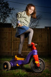 Biker. Little angry Caucasian girl riding a red bike in the backyard of the house Royalty Free Stock Photography
