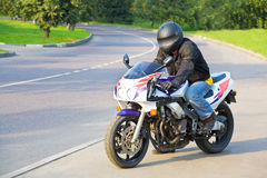 Biker. On the sport bike dreesed in ptotective wear near road Royalty Free Stock Images