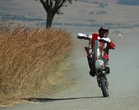 Biker. Showing off on a dirt road stock image