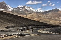 A biker on a adventure trip on a road deep inside the valley of Ladakh, India Royalty Free Stock Photography