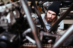 Biker Assembling Motorcycle in Garage. Portrait of focused tattooed man working in garage tuning up motorcycle stock photography
