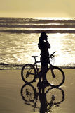 Biker by the beach. Young woman and bike talking by phone by the sea shore royalty free stock photos