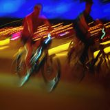Biker on the bicycle close-up, night city lights, bokeh. Sport, healthy lifestyle concept, motion blur effect. Abstract Royalty Free Stock Image
