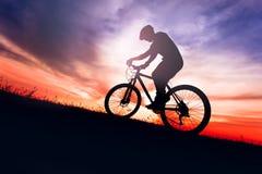 Biker on bike with sky background on sunsetSilhouette of a biker on bike with sky background on sunsetSilhouette. Silhouette of a biker on bike with sky Stock Photo