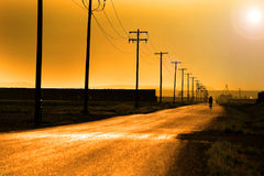 Biker Biking on Country Road with Power Lines and Poles. Biker biking on country road with power poles and lines Stock Photos