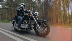 A biker in black rides along an empty two lane road. 4K. stock video