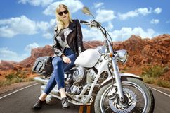 Biker blonde girl. In black leather jacket sitting on motorcycle stock photography