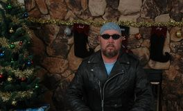 Biker Boy at Christmas Time. Biker in leathers in front of a Christmas Tree Royalty Free Stock Image