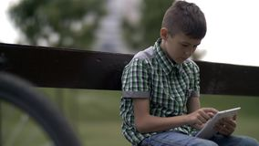 Biker boy in hat sitting on bench in park after riding bicycle uses tablet royalty free stock photography