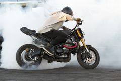 Biker burning tire and creating smoke on bike in motion stock photo