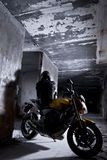 Biker in a cage. Biker with a sportbike inside of an abandoned building. Freedom concept royalty free stock image