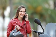 Biker calling on phone on a motorbike on the street. Happy biker calling on smart phone on a motorbike on the street Royalty Free Stock Photo