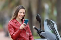 Biker checking phone on her motorbike on the street. Happy biker checking smart phone on her motorbike on the street Stock Photography