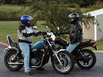 Biker Couple. Young Couple on motorcycles making plans Stock Image