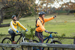 Biker couple cycling and pointing in distance Royalty Free Stock Images