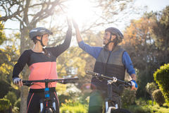 Biker couple giving high five while riding bicycle in countryside Royalty Free Stock Images