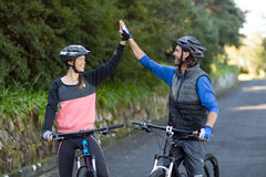 Biker couple giving high five while riding bicycle on the road Royalty Free Stock Images