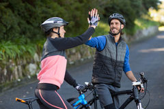 Biker couple giving high five while riding bicycle on the road Royalty Free Stock Photography
