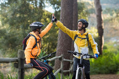 Biker couple giving high five to each other in countryside Stock Photo