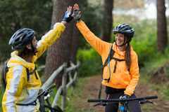 Biker couple giving high five to each other in countryside Royalty Free Stock Image