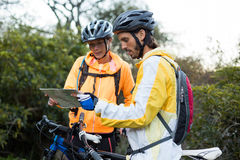 Biker couple looking at a map Stock Photography