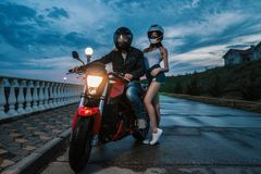Biker couple man and woman on a black and red color sport motorcycle Royalty Free Stock Image