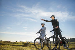 Biker couple with mountain bike pointing in distance at countryside Royalty Free Stock Photos