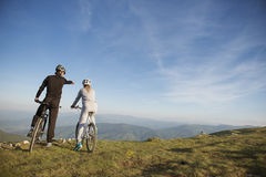 Biker couple with mountain bike pointing in distance at countryside.  Stock Photo