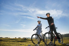 Biker couple with mountain bike pointing in distance at countryside Royalty Free Stock Images