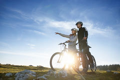 Biker couple with mountain bike pointing in distance at countryside.  Royalty Free Stock Photos