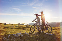 Biker couple with mountain bike pointing in distance at countryside.  Royalty Free Stock Images