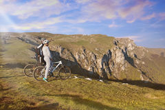 Biker couple with mountain bike pointing in distance at countryside.  Stock Image
