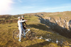 Biker couple with mountain bike pointing in distance at countryside.  Royalty Free Stock Photography