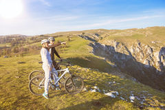 Biker couple with mountain bike pointing in distance at countryside.  Royalty Free Stock Photo