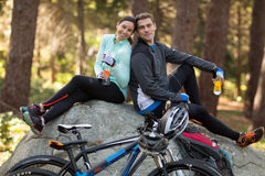 Biker couple sitting on rock in forest Stock Photo