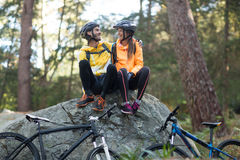 Biker couple sitting on rock and interacting with each other Stock Photos