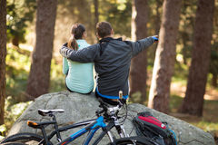 Biker couple sitting on rock pointing at distance in forest Stock Photos