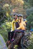 Biker couple sitting on a tree stump Stock Images