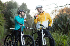 Biker couple standing with bicycle drinking water in forest Royalty Free Stock Photography