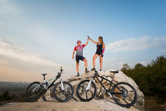 Biker couple standing on a rock and giving high five Royalty Free Stock Image