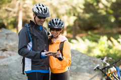 Biker couple using mobile phone in forest stock images