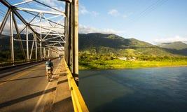 Biker crossing a bridge in Costa Rica. Biker on a metal bridge looking at the landscape stock image