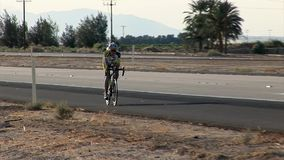 Biker cycles by in high speed stock video footage
