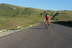 Biker cycling on road Royalty Free Stock Image