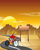A biker at the desert with an empty signboard Royalty Free Stock Image