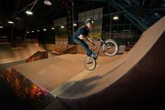 Biker doing bar spin trick. In wooden ramp Stock Image