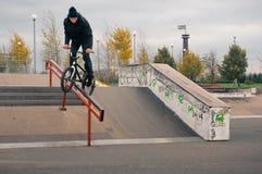 Biker doing crank slide grind trick. Down to red rail Stock Images