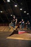 Biker doing manual to bar spin trick Royalty Free Stock Photos