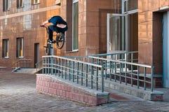 Biker doing rail hop trick back view Stock Image