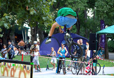 Biker doing stunts in city park Royalty Free Stock Images
